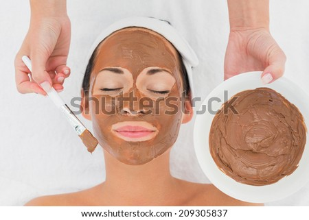 Smiling brunette getting a mud treatment facial in the health spa - stock photo