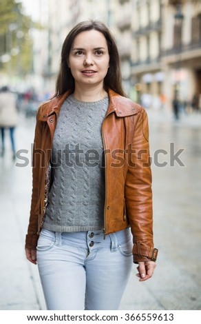 Smiling brunette girl with long hair chasing city streets - stock photo