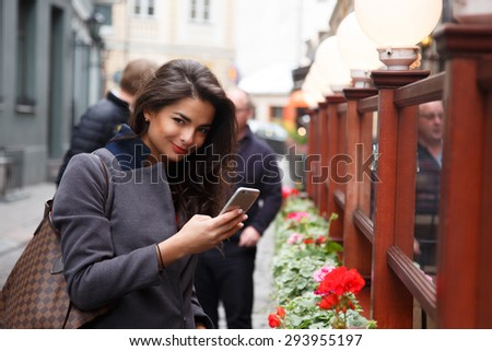 Smiling brunette girl with smartphone on the street. - stock photo