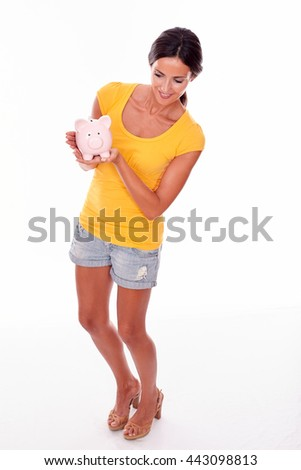 Smiling brunette holding a pink piggy bank while looking at the piggy bank and wearing a yellow t-shirt and short jeans isolated - stock photo