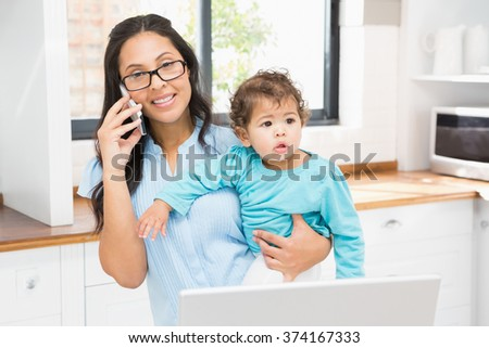 Smiling brunette holding her baby and using laptop on phone call in the kitchen - stock photo