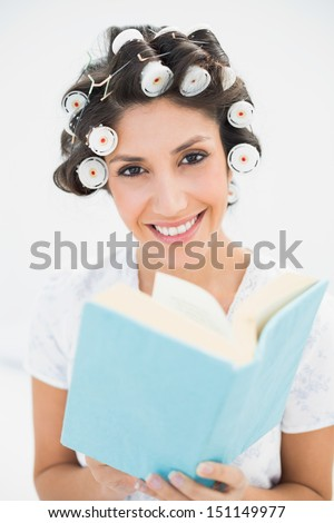 Smiling brunette in hair rollers holding a book on bed at home in bedroom - stock photo