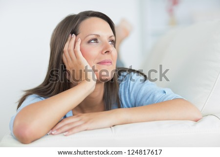 Smiling brunette lying on sofa and looking up - stock photo