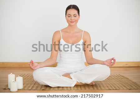 Smiling brunette sitting in lotus pose looking at camera in a white room - stock photo