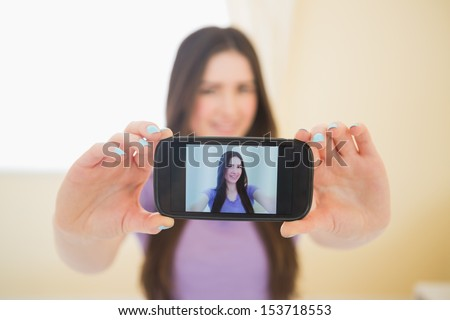 Smiling brunette taking a photo of herself with her mobile phone in a bedroom - stock photo
