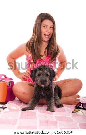 smiling brunette teenage girl in swimsuit at the beach with her shipoo dog (studio setting with beach and personal items) isolated on white background - stock photo