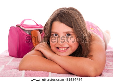 smiling brunette teenage girl in swimsuit lying at the beach (studio setting with bag, pink towel, sun lotion and little stones) isolated on white background - stock photo
