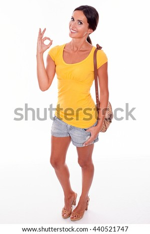 Smiling brunette with brown handbag and a thumb in her pocket looking at camera and gesturing a perfect sign while wearing a yellow t-shirt, isolated - stock photo