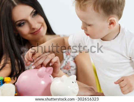 Smiling brunette woman and little boy putting pin coins into pink piggybank slot. Mother and son playing. Making family savings and effective investment concept. Future needs deposit. Focus on hand - stock photo