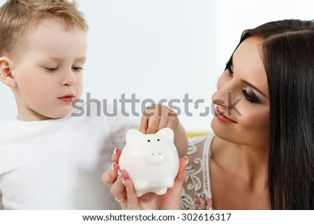 Smiling brunette woman and little boy putting pin coins into white piggybank slot. Mother and son playing. Making family savings and effective investment concept. Future needs deposit - stock photo