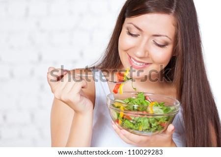 smiling brunette woman eating fresh vegetable salad - stock photo