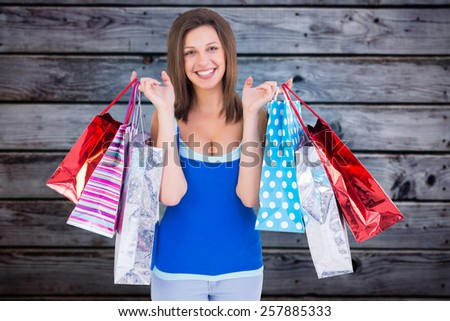 Smiling brunette woman holding shopping bags against grey wooden planks - stock photo