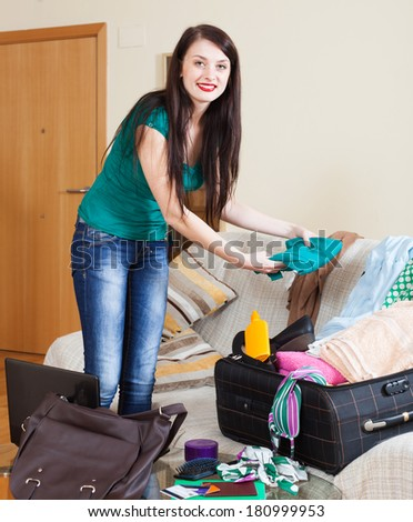 Smiling brunette woman packing suitcase for travel - stock photo