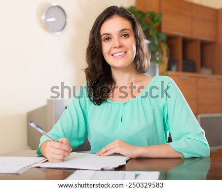 Smiling brunette woman reading document at office - stock photo