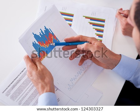 Smiling business colleagues sitting behind a desk discussing statistics with bar graphs in their hands - stock photo