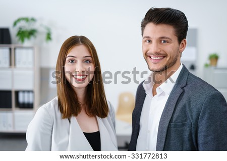 smiling business colleagues standing at the office and looking at camera - stock photo