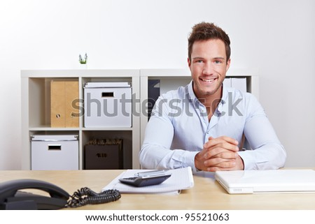 Smiling business consultant in office at desk - stock photo