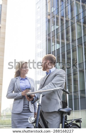 Smiling business couple talking outside office building - stock photo