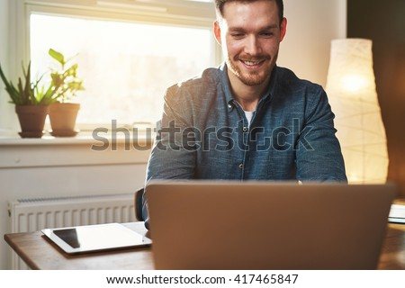 Smiling business entrepreneur at work in his office at home reading data on the laptop computer with satisfaction as he checks his website - stock photo