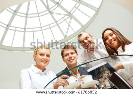 Smiling business group looking above camera - stock photo