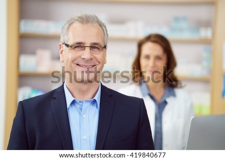 Smiling business man at drug store counter being attended by female pharmacist besides medicine stocked shelves - stock photo