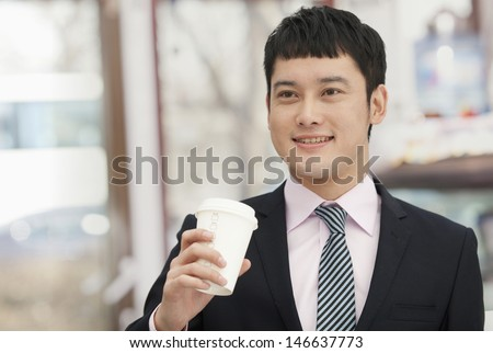 Smiling business man holding coffee cup - stock photo