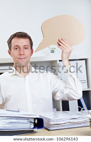 Smiling business man holding empty comic speech bubble - stock photo