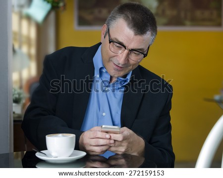 Smiling business man looking at his smart phone while text messaging - stock photo