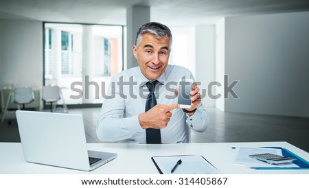 Smiling business man pointing at his smart phone and showing a mobile banking app - stock photo