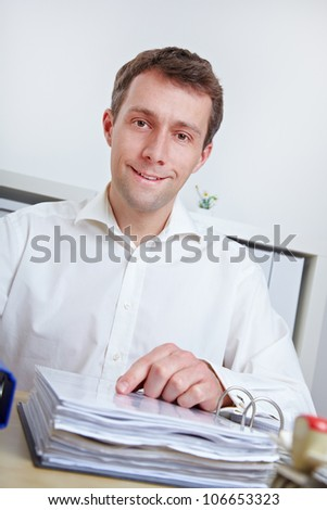 Smiling business man sitting at his desk in the office - stock photo