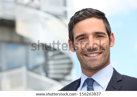 Smiling business man standing outside office building - stock photo
