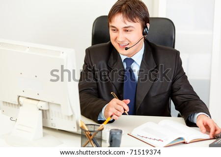 Smiling  business man with  headset sitting at office desk and looking at computer monitor - stock photo