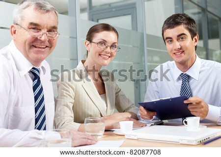 Smiling business partners looking at camera in office - stock photo