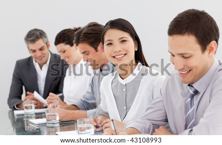 Smiling business partners taking notes in a meeting in the office - stock photo