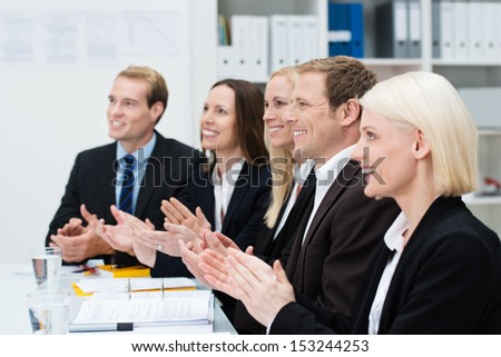 Smiling business people clapping their hands at the end of a meeting or presentation or in recognition of an achievement by one of their colleagues - stock photo