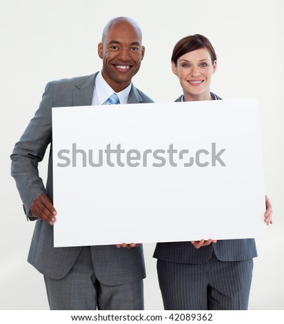 Smiling business people holding white card against white background - stock photo