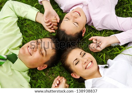 Smiling business people lying on grass and holding by hands - stock photo