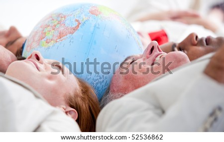Smiling business people lying on the floor around a terrestrial globe - stock photo