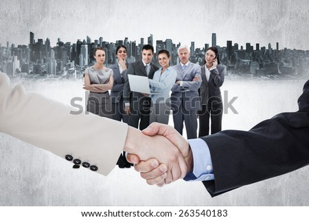Smiling business people shaking hands while looking at the camera against cityscape - stock photo