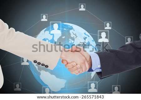 Smiling business people shaking hands while looking at the camera against global technology background - stock photo