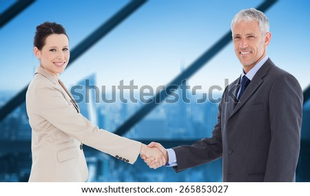 Smiling business people shaking hands while looking at the camera against room with large window looking on city - stock photo