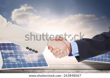 Smiling business people shaking hands while looking at the camera against solar panels on floorboards in the sky - stock photo