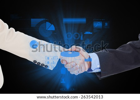 Smiling business people shaking hands while looking at the camera against technology interface - stock photo