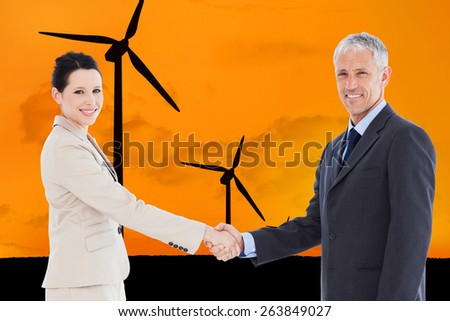 Smiling business people shaking hands while looking at the camera against wind turbines with a sunset - stock photo