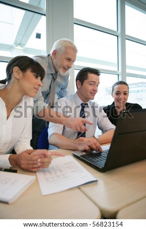 Smiling business people sitting at a desk in front of a laptop computer - stock photo