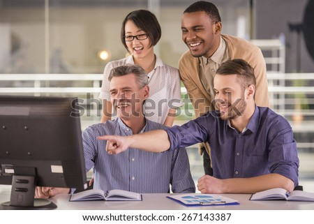 Smiling business people team at a meeting in a light and modern office - stock photo