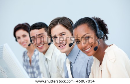 Smiling business people using headset in a call center - stock photo