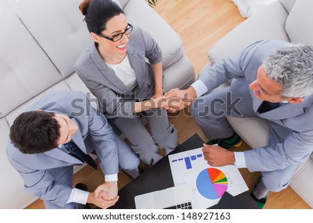 Smiling business shaking hands during meeting on sofa at office - stock photo