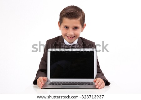 smiling business student at a business suit sitting at his desk and shows laptop, picture with depth of field - stock photo