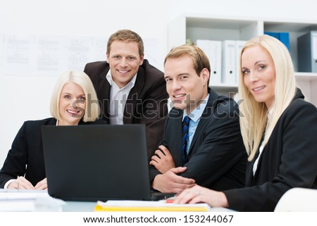 Smiling business team at work in the office seated around a table and laptop computer discussing their strategy - stock photo